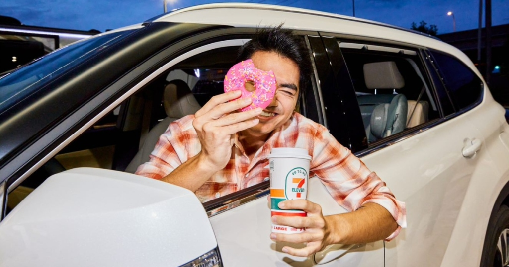 National Coffee Day freebies & deals - man holding coffee and doughnut out car window