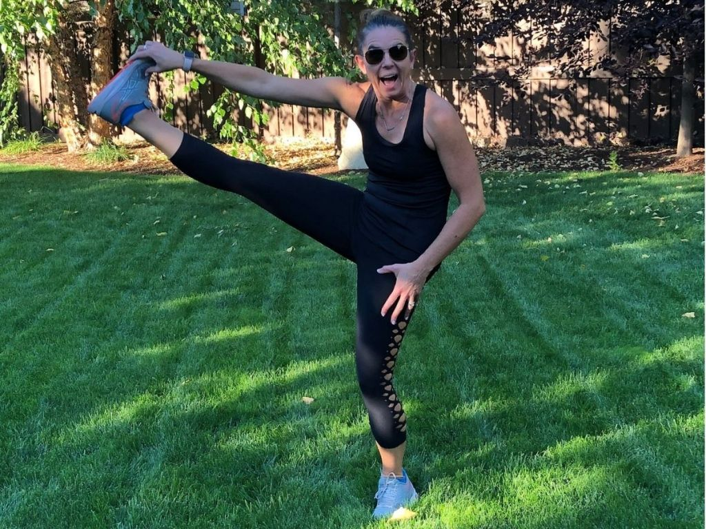 woman outdoors dressed in black workout gear lifting her leg up with her hand