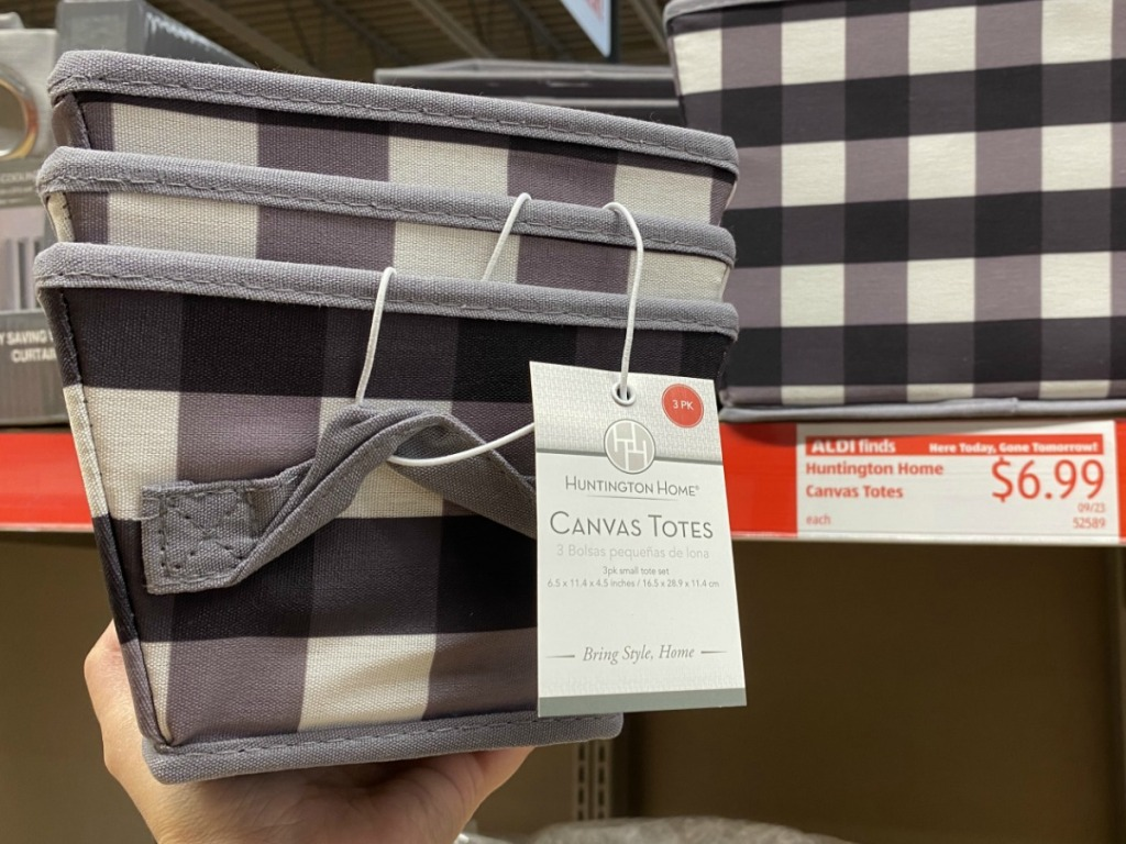Black and white canvas totes in a three pack in hand near in-store display