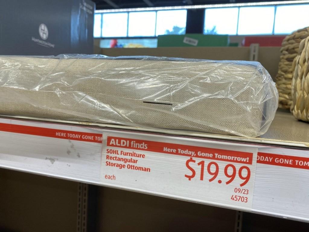 Large beige storage ottoman in package on shelf