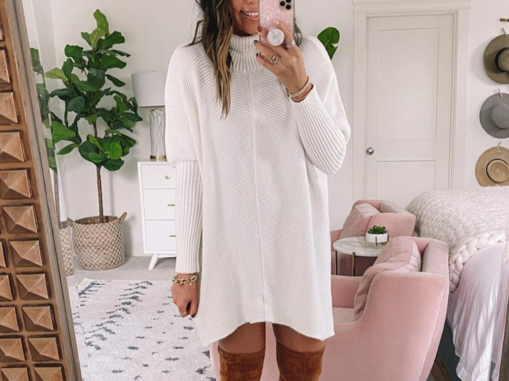 woman taking selfie in white sweater and high boots