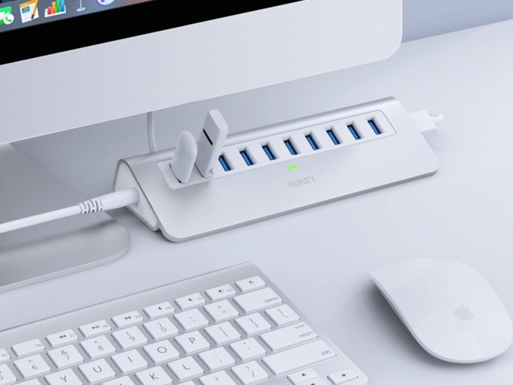 Silver and White Aukey multiple USB hub plugged next to a mac screen, keyboard and mouse