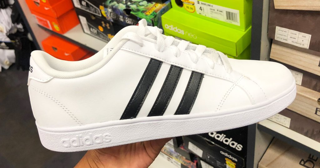 person holding up a white adidas sneaker with three black stripes on the side