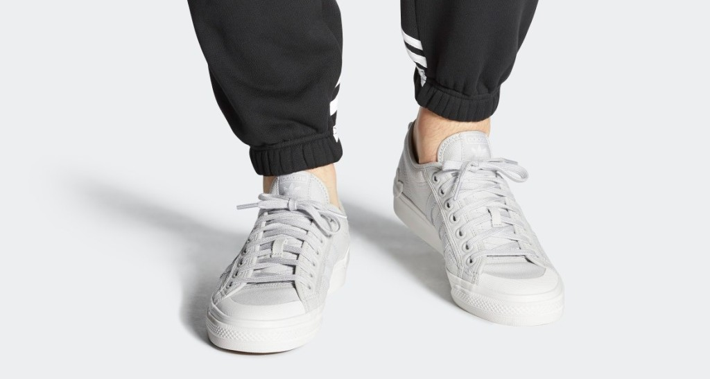 person wearing grey sneakers