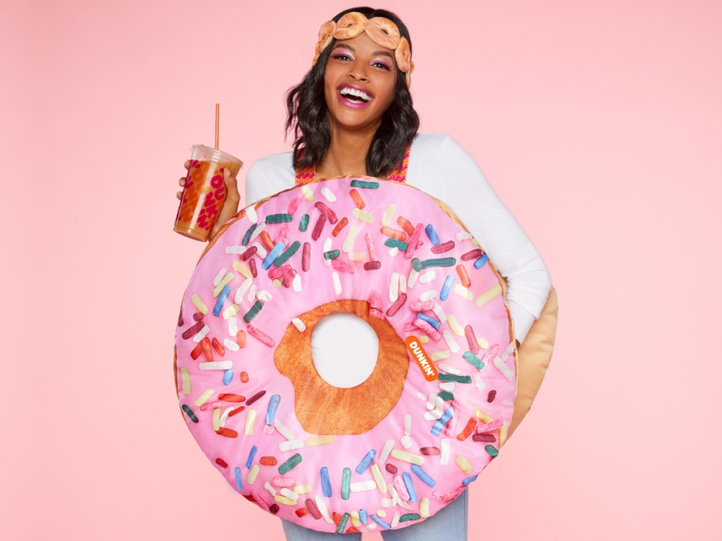 woman in pink sprinkle donut costume holding cup of iced coffee and light pink background