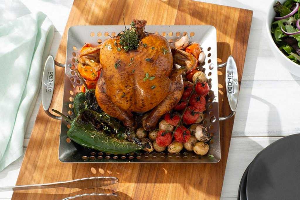 stainless steel chicken roaster pan with whole roasted chicken on it on a cutting board