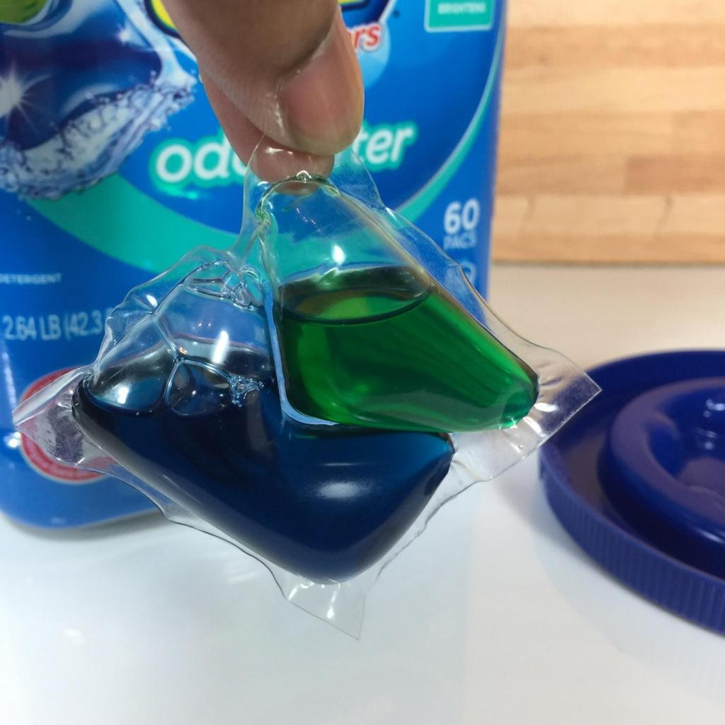 Hand holding one All Mighty Pac detergent capsule