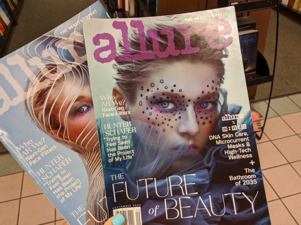 hand holding two allure magazines