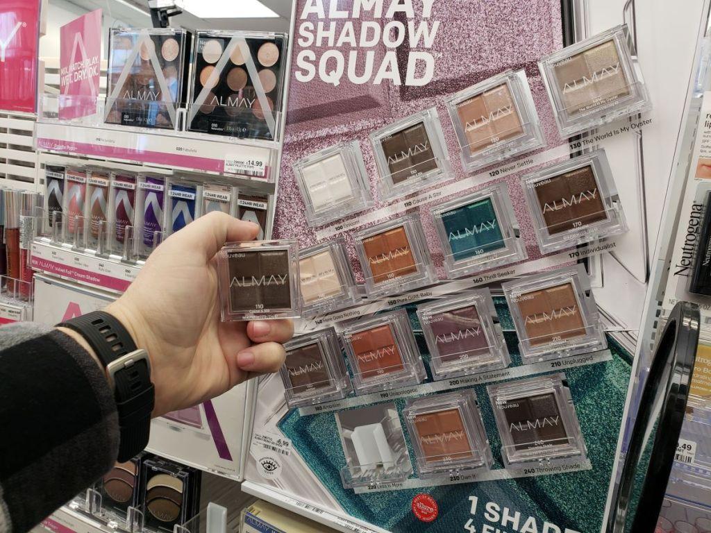 hand holding Almay eyeshadow by eyeshadow display