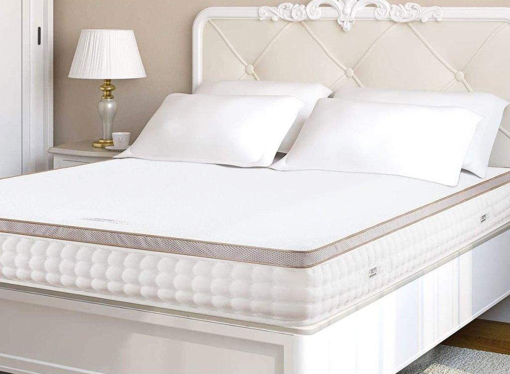 white memory foam mattress topper on a mattress with pillows on top