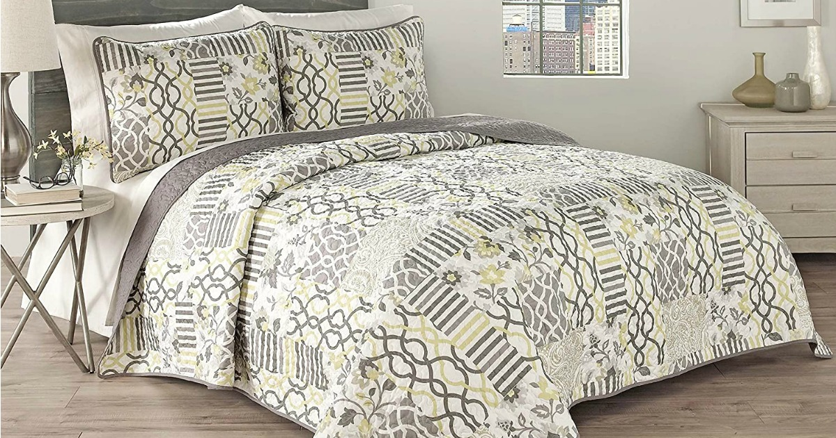 Bed made up with a quilt and matching pillow cases in gray and yellow floral print