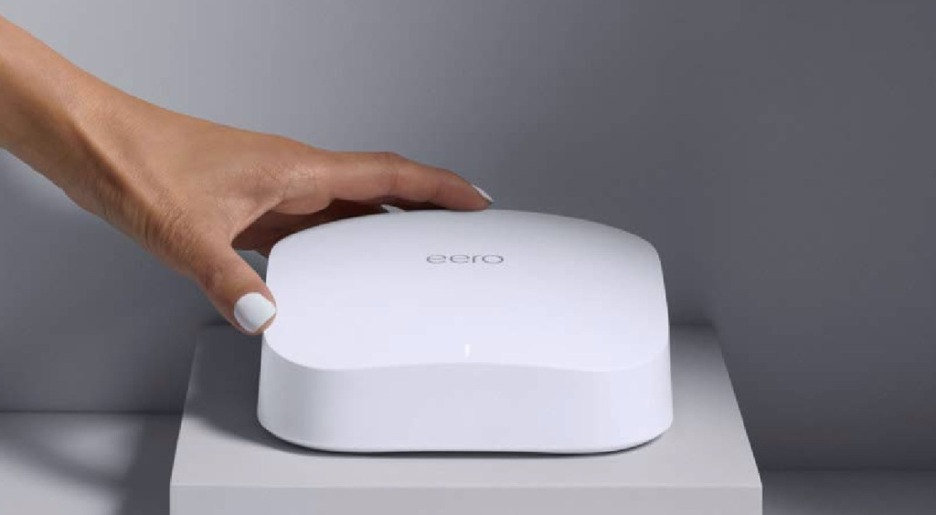 hand touching white WiFi router