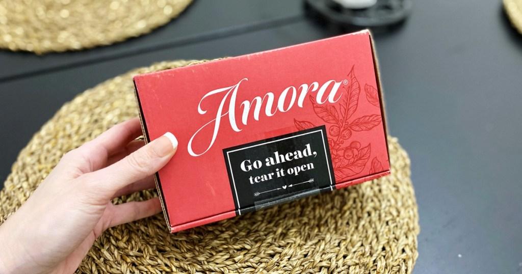 hand holding box of amora coffee