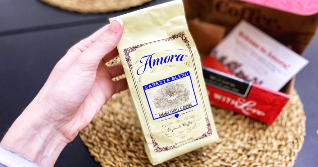 hand holding Amora Caramel Vanilla Coffee