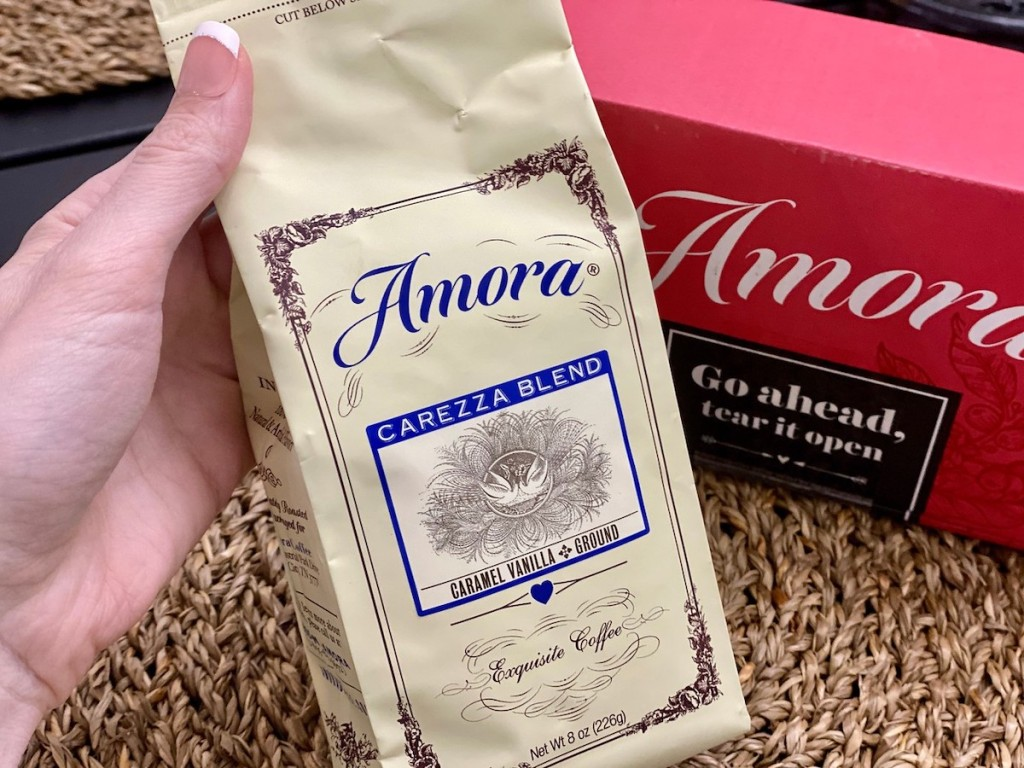 hand holding bag of amora with amora box in the background