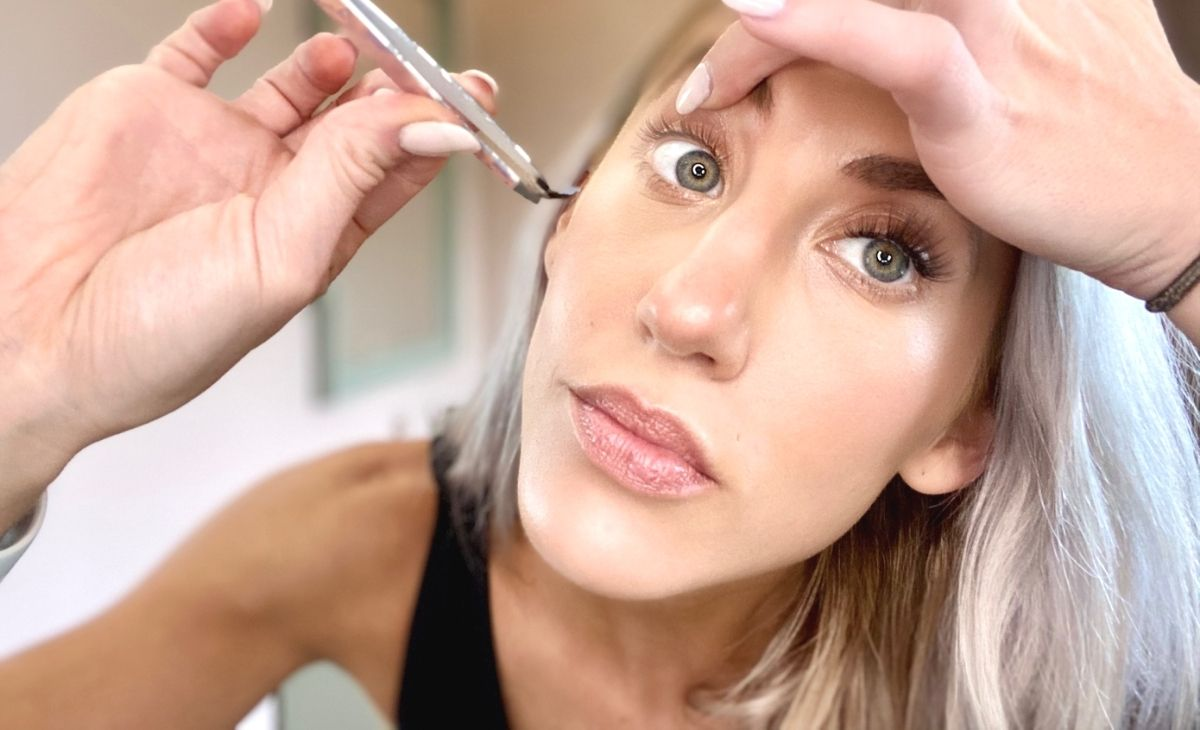 A woman applying false eyelashes