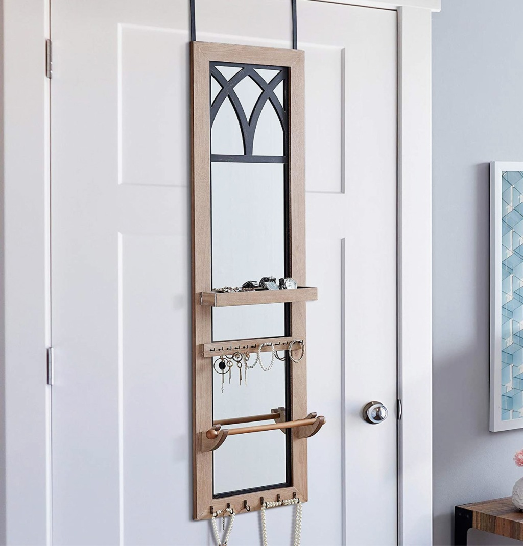 mirrored jewelry organizer hanging on the back of a bedroom door