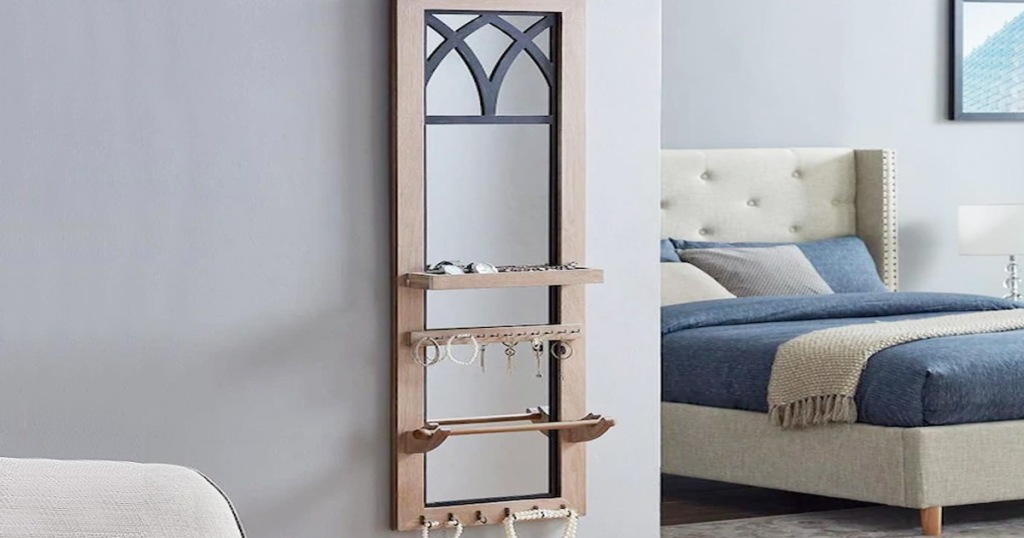 wood framed mirrored jewelry organizer on bedroom wall with hanging jewelry