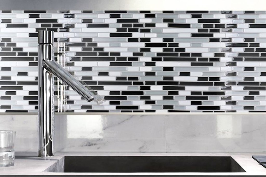 black, grey, and white peel and stick tile backsplash on wall in front of sink