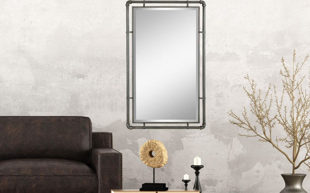 metal pipe framed wall mirror on wall next to couch and accent table