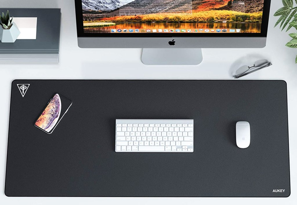large black gaming keyboard under white keyboard and mouse in front of imac