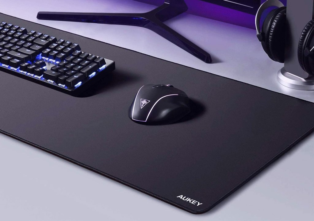 large black gaming mousepad under a keyboard and mouse on grey desk
