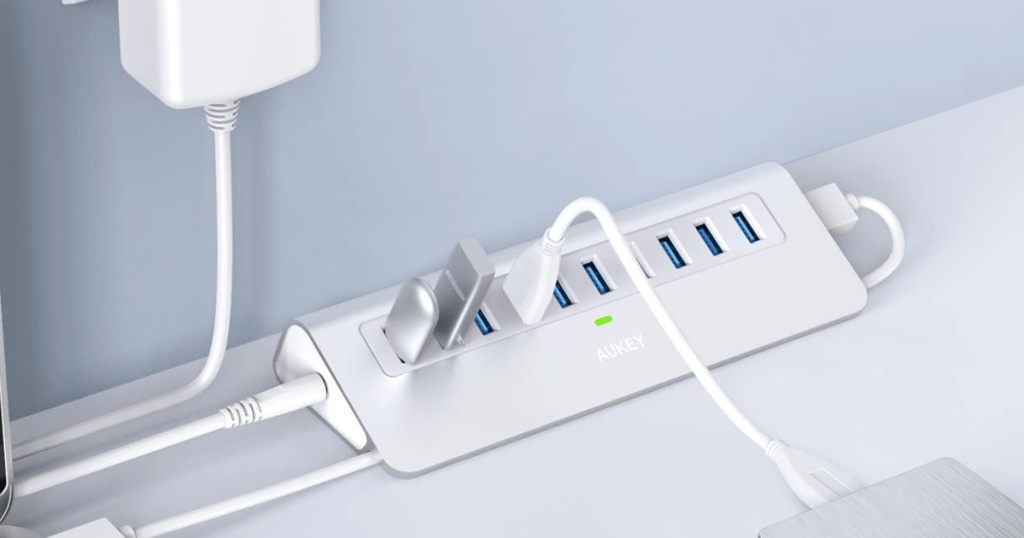 Silver and White Aukey multiple USB hub plugged into the wall