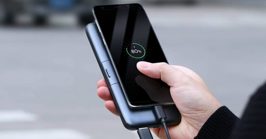 man holding portable charger and phone