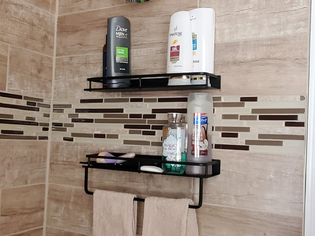 2 shower caddy racks attached to a shower wall with beauty products on the shelves