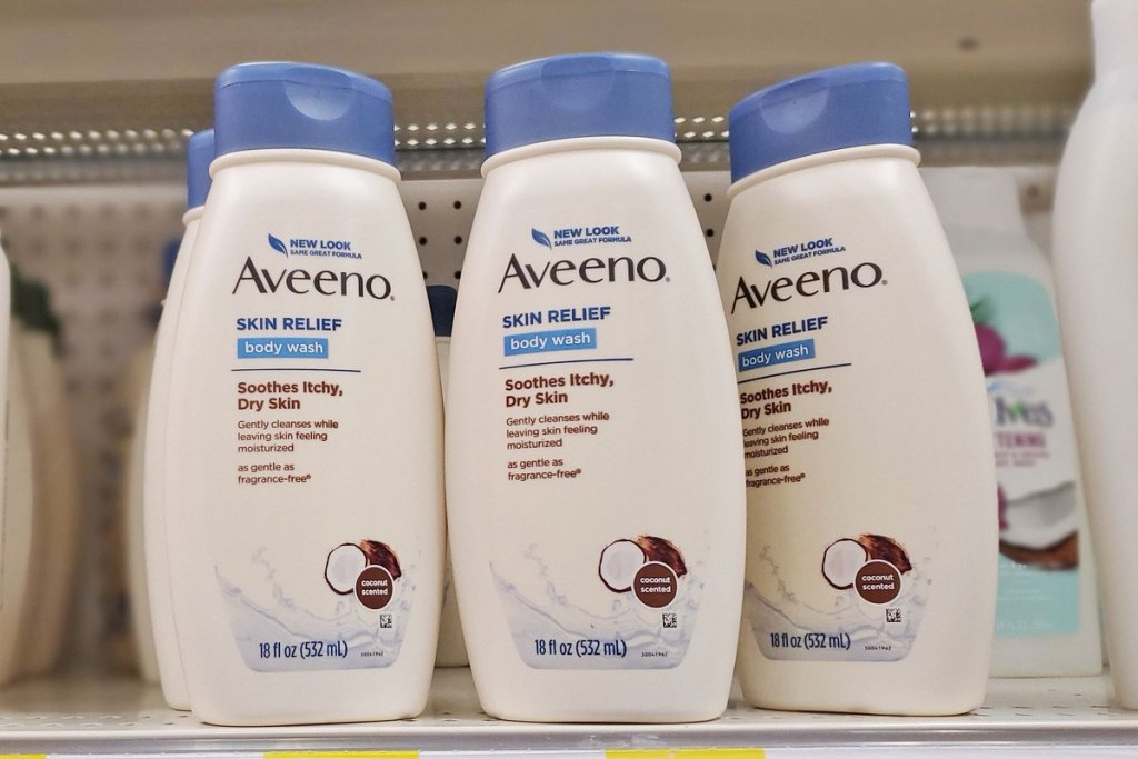 white and blue bottles of aveeno body wash in coconut scent on store shelf