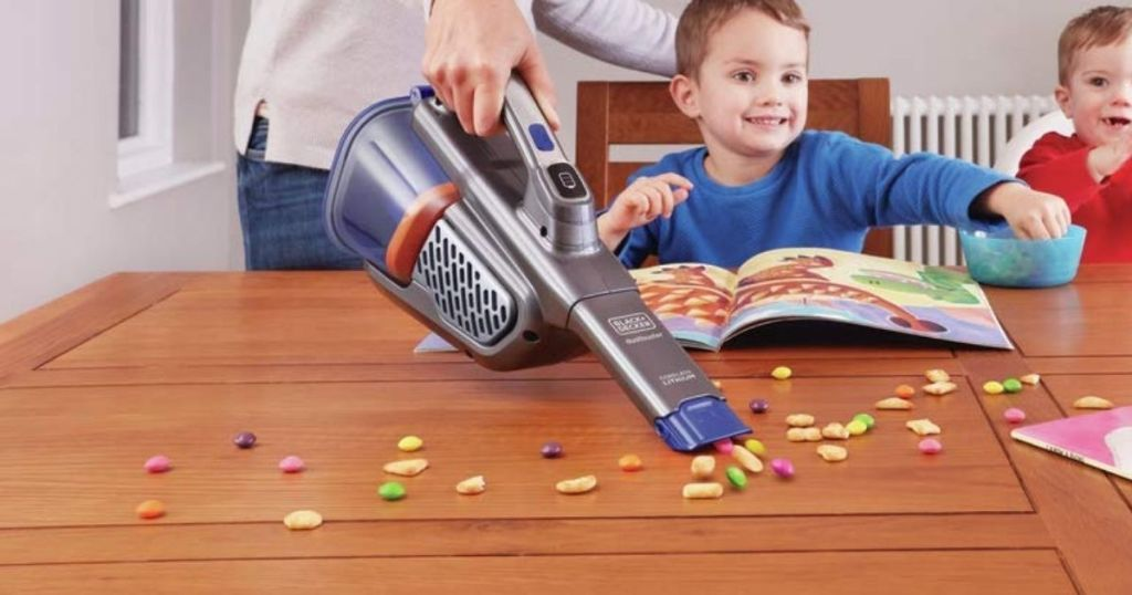 woman using BLACK+DECKER Dustbuster Handheld Vacuum Pets AdvanceClean+ to vacuum up candy on table with kids