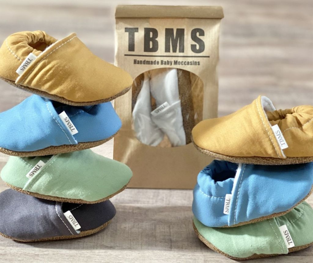 stack of baby moccasins next to a bag