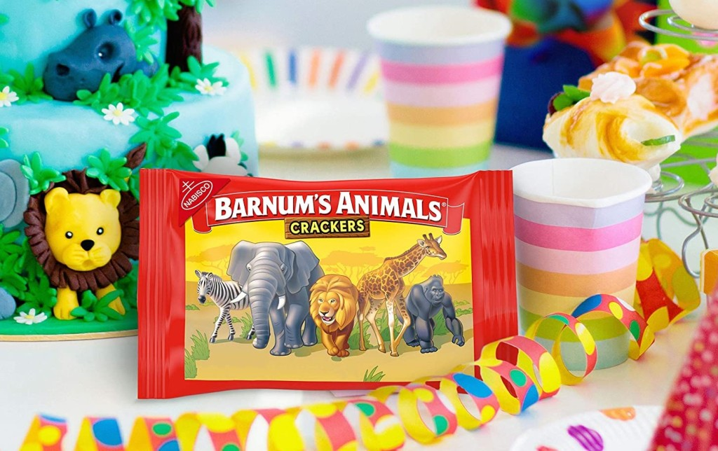 bag of animal crackers next to birthday cake and party decorations