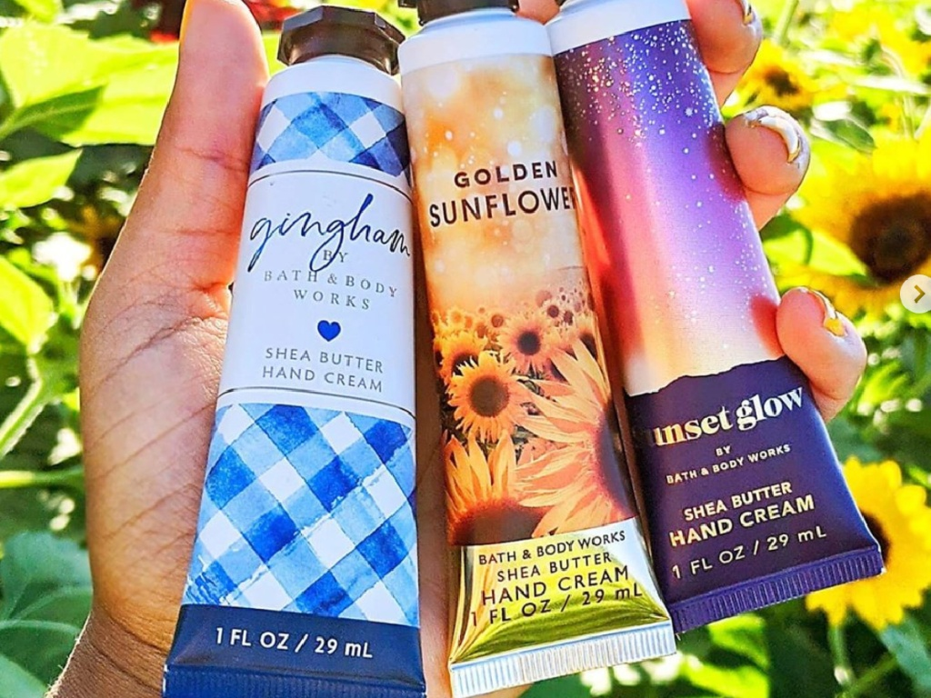 hand holding bath & body works fun size hand creams in a field of sunflowers