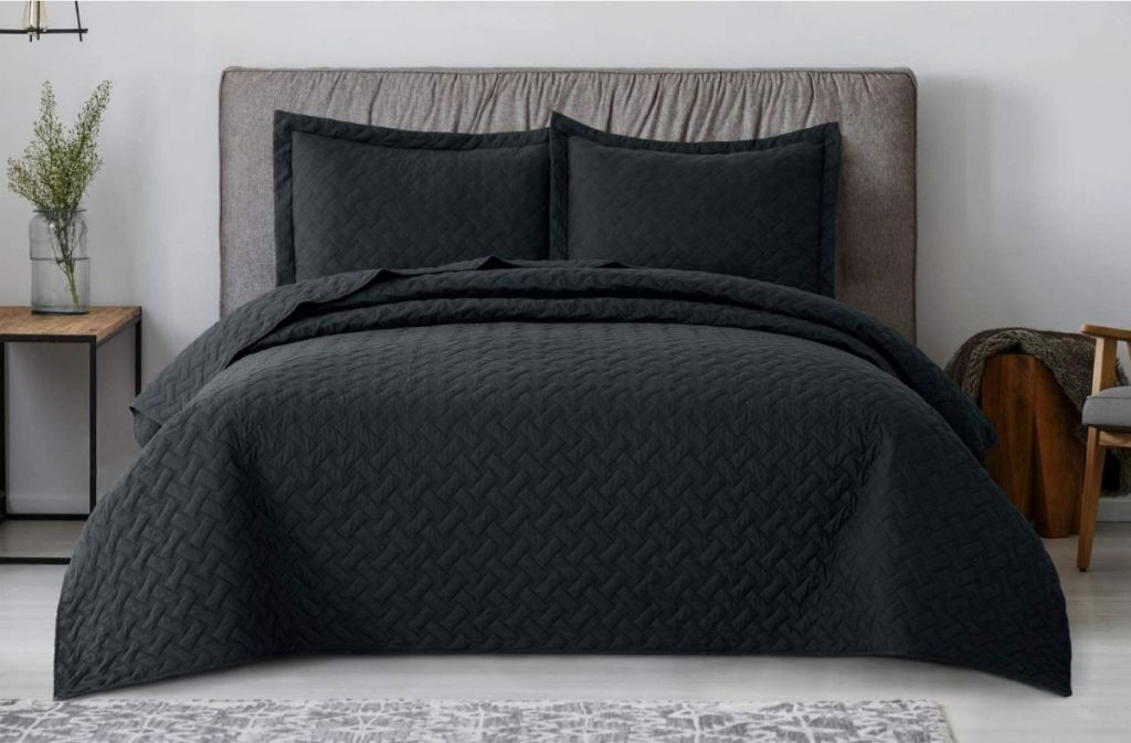 bed with a black quilt on it