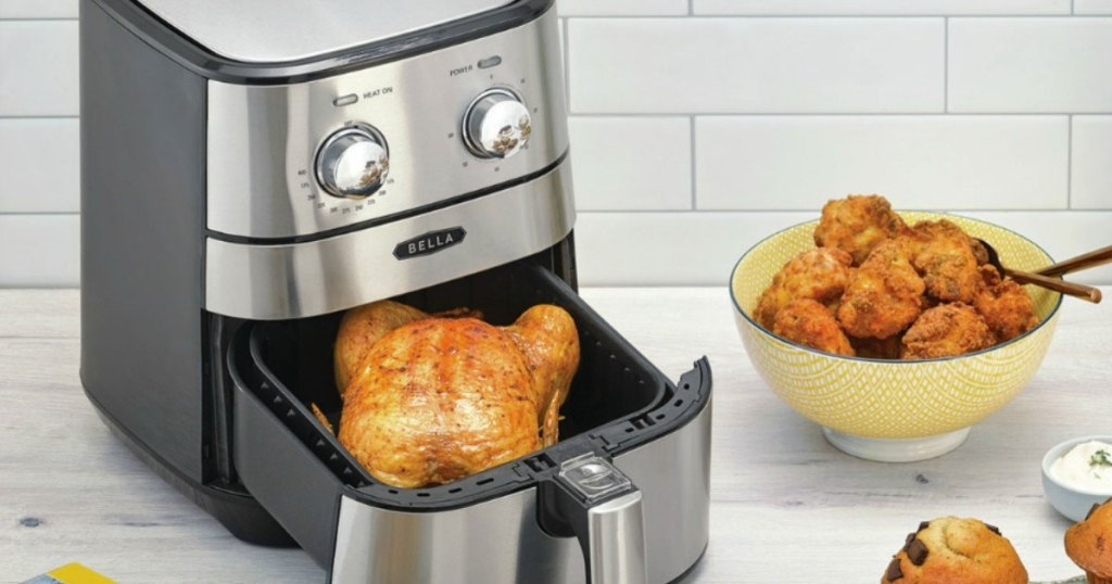 stainless steel air fryer with two adjustment knobs on kitchen counter with fried chicken