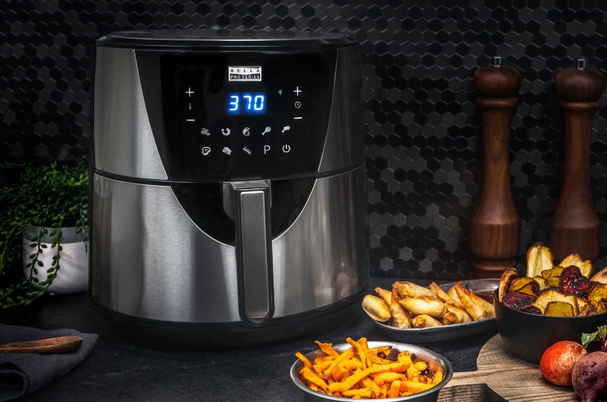 air fryer with fried food around it