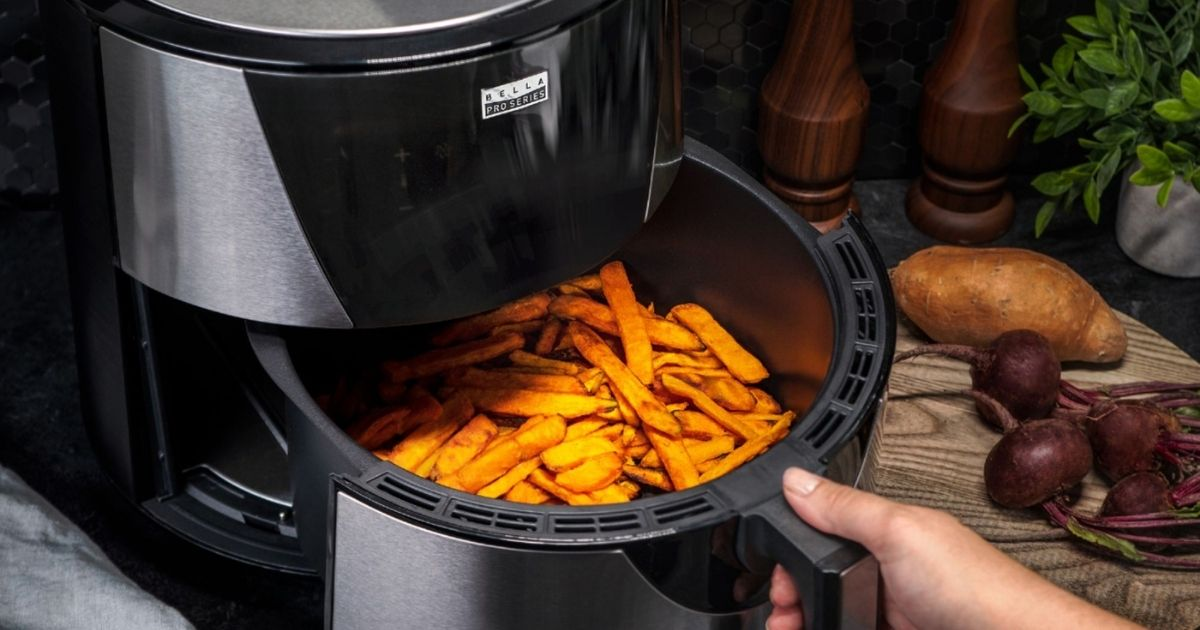 hand pulling out a basket of food from an air fryer