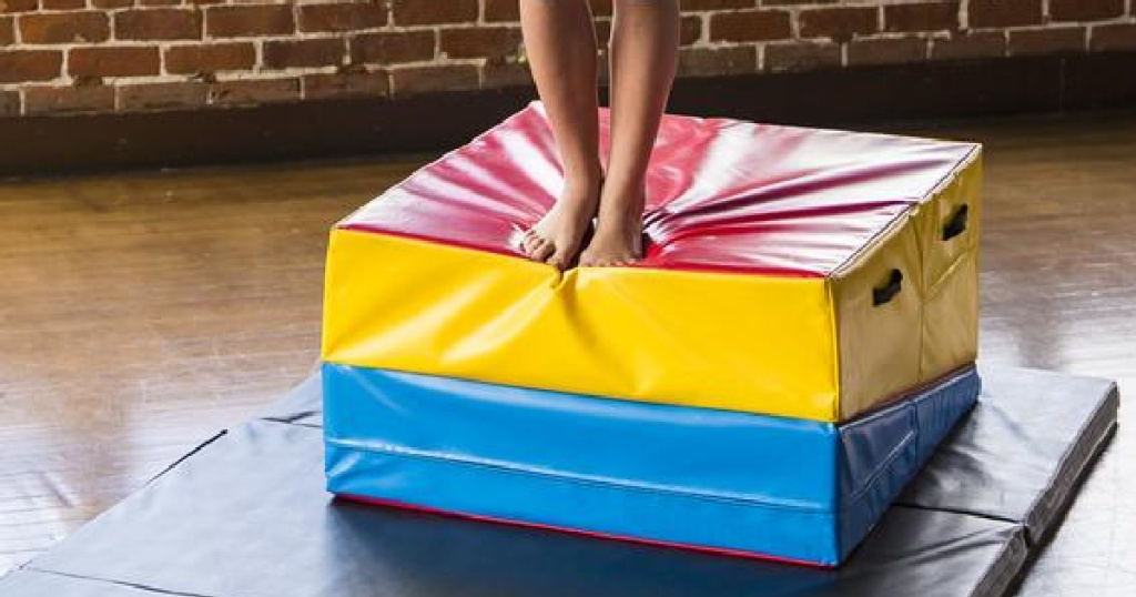 person standing on top of a colorful folded incline wedge