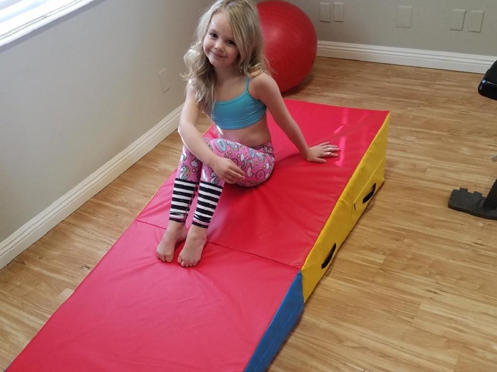 little girl sitting on a gymnastics incline wedge