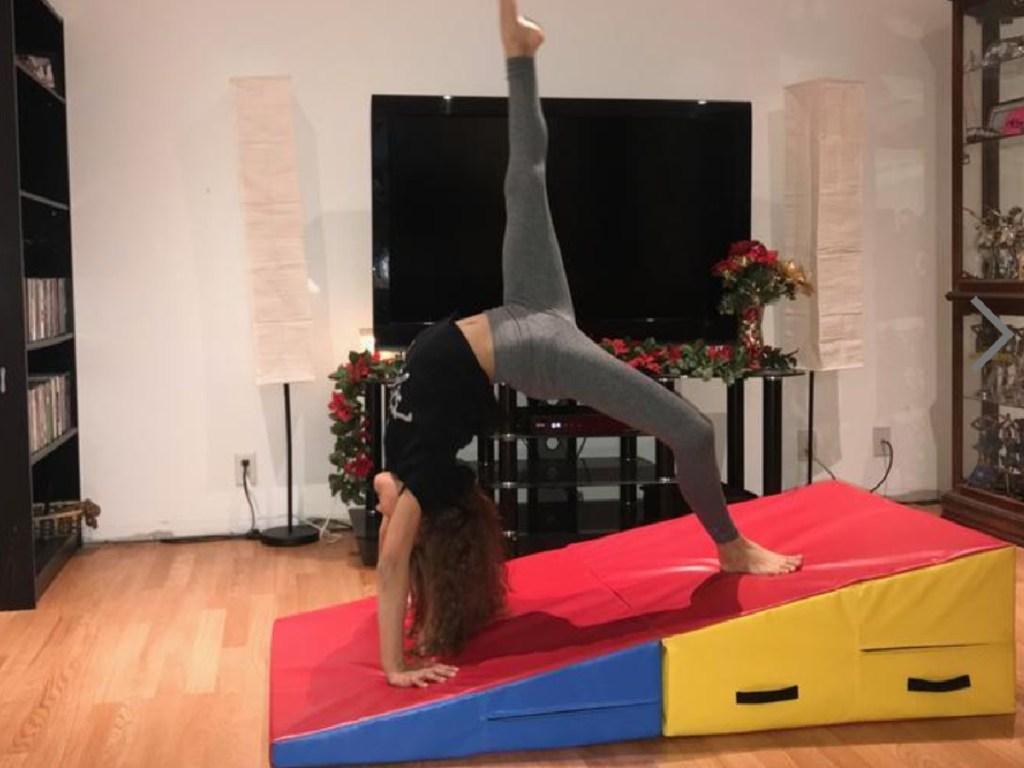girl doing a backwards walkover on a gymnastics incline wedge mat