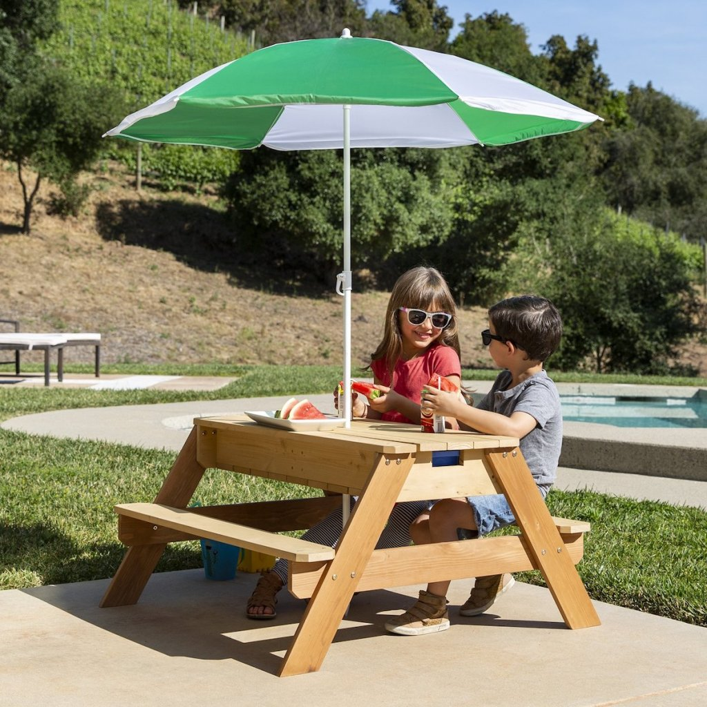 two kids sitting at picnic table with umbrella