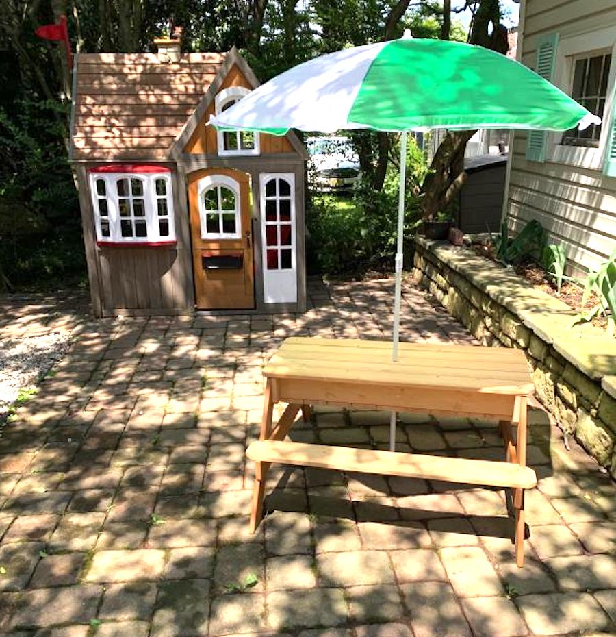 cute picnic table with umbrella on wooden patio