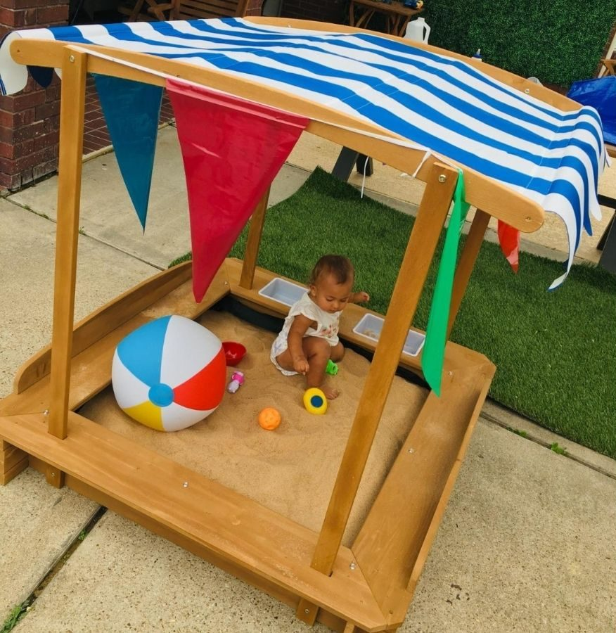 toddler playing in cabana style sandbox with a beach ball and other sand toys