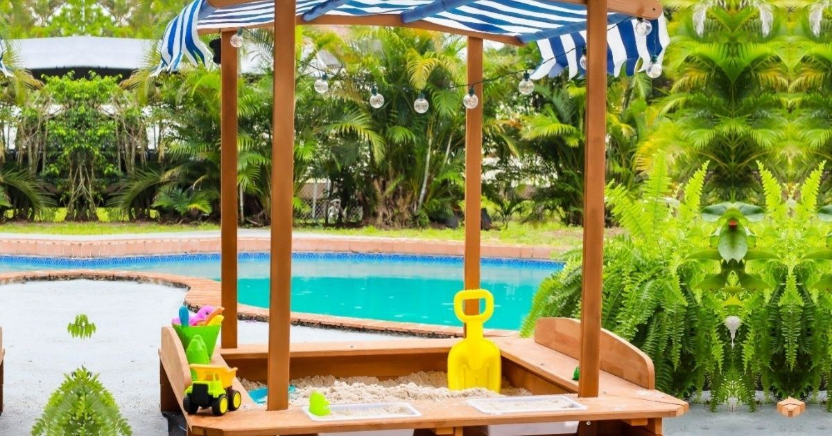 Kids wooden sandbox with canopy near a pool and lots of greenery
