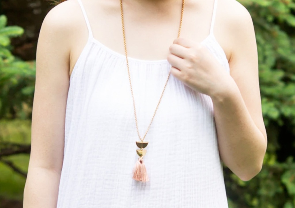 woman in white tank top and long pendant necklace in gold and blush colors