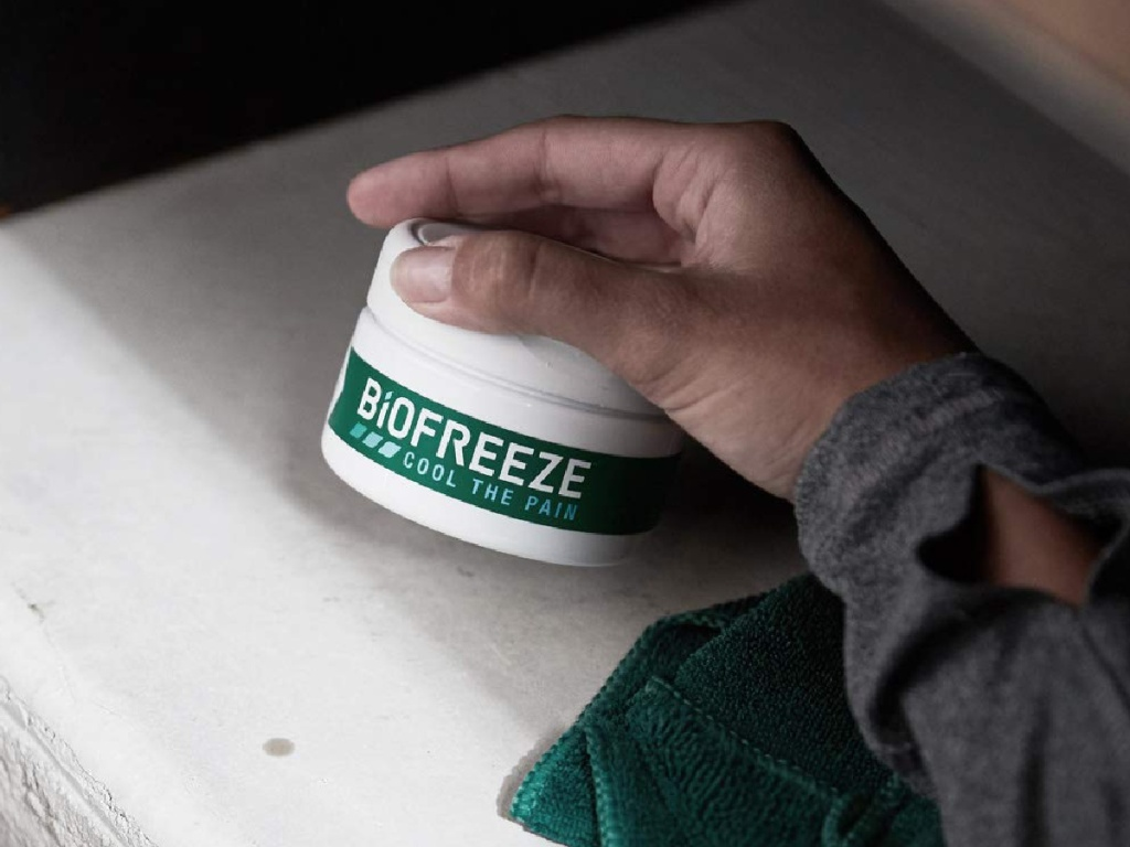 hand holding a 3oz jar of Biofreeze pain relief cream
