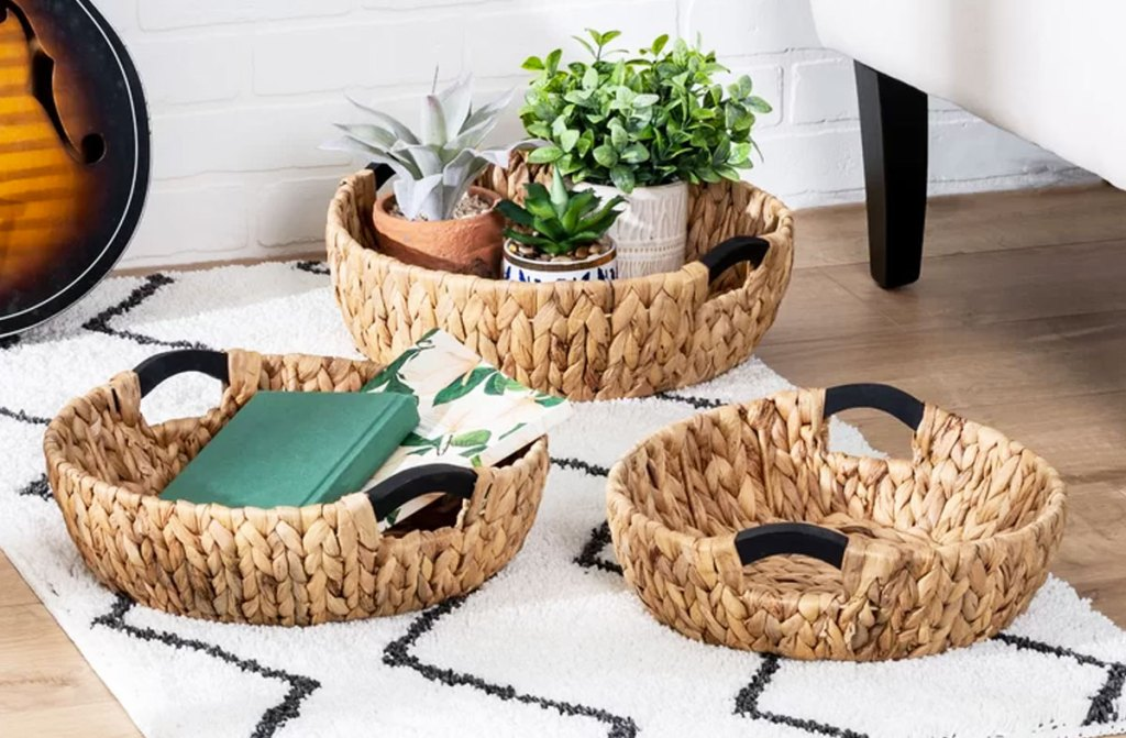 three woven baskets on area rug with books and potted plants inside