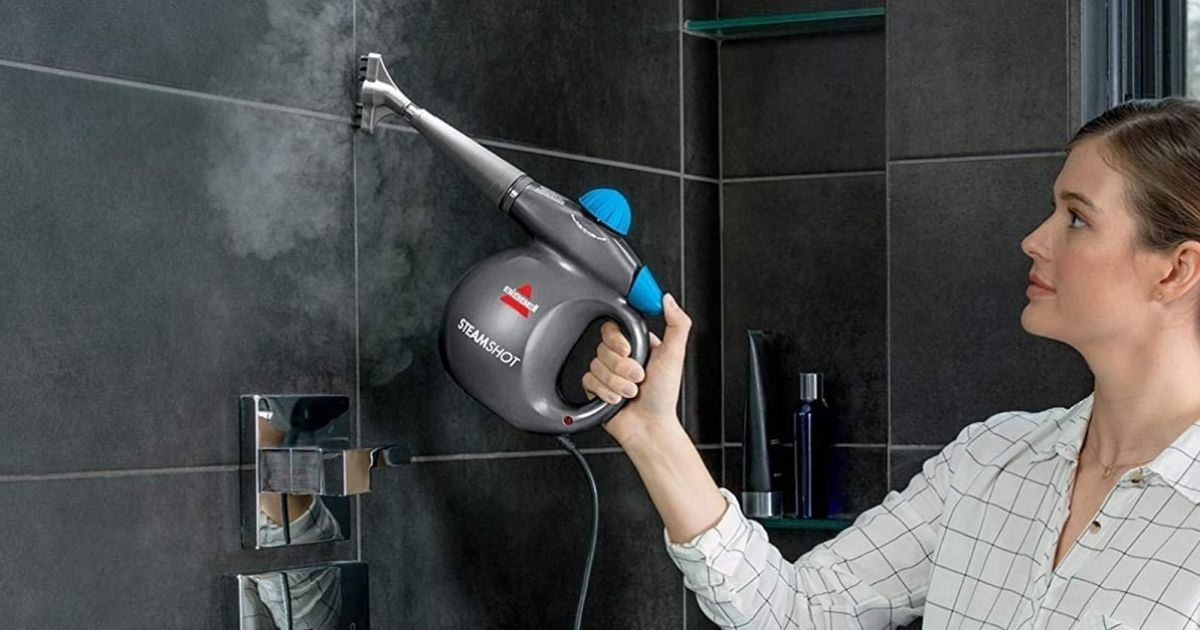 woman steam cleaning tiles