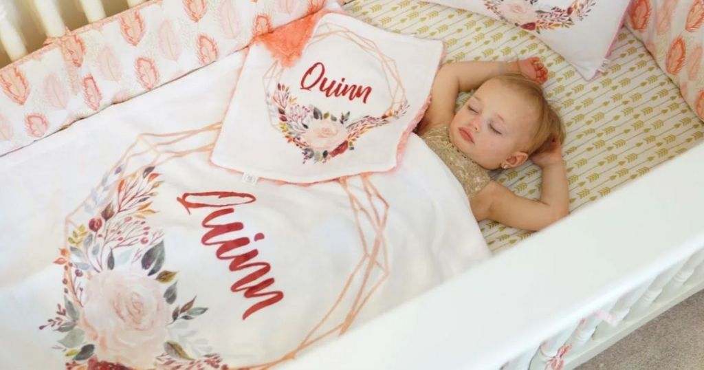 baby girl sleeping in white crib with personalized Quinn baby blanket over her